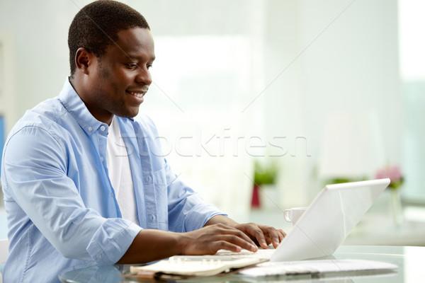 Met behulp van laptop afbeelding jonge afrikaanse man typen Stockfoto © pressmaster