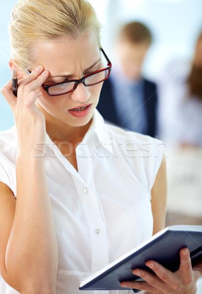 Au portret niespokojny sekretarz patrząc notatnika Zdjęcia stock © pressmaster