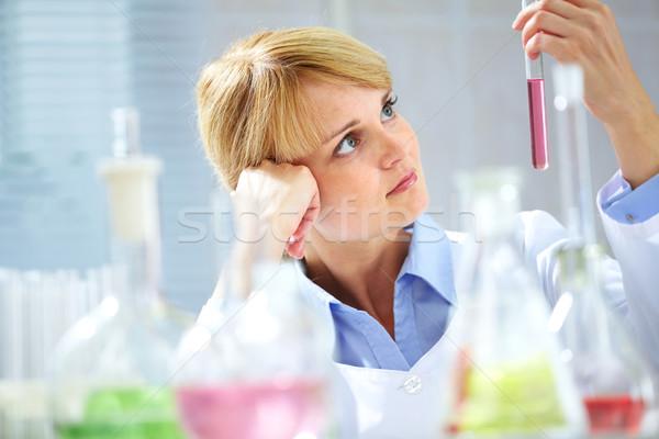 Pensativo químico jovem olhando tubulação líquido Foto stock © pressmaster