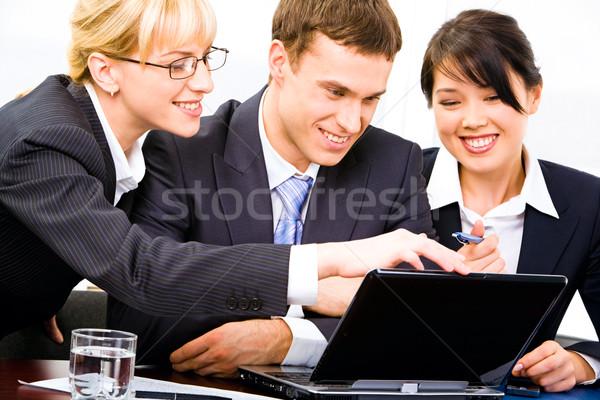 Trabalho em equipe três pessoas de negócios juntos em torno de tabela Foto stock © pressmaster
