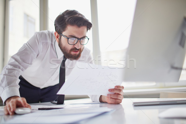 Complicado esboço intrigado empresário olhando papel Foto stock © pressmaster