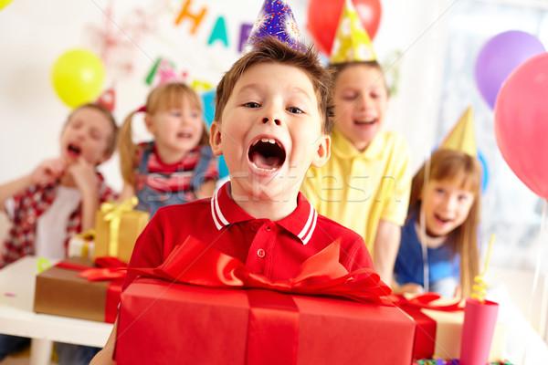 örömteli fiú nagy piros néz kamera Stock fotó © pressmaster
