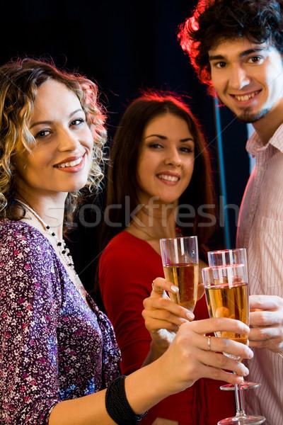 Tres personas gafas champán mirando cámara Foto stock © pressmaster