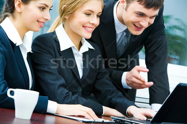 Negocios interacción retrato equipo de negocios mirando portátil Foto stock © pressmaster