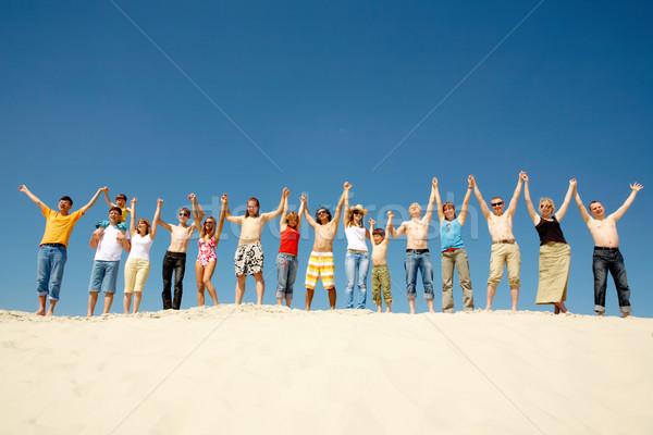 Stock fotó: Kép · sok · barátok · áll · homokos · tengerpart · karok · a · magasban