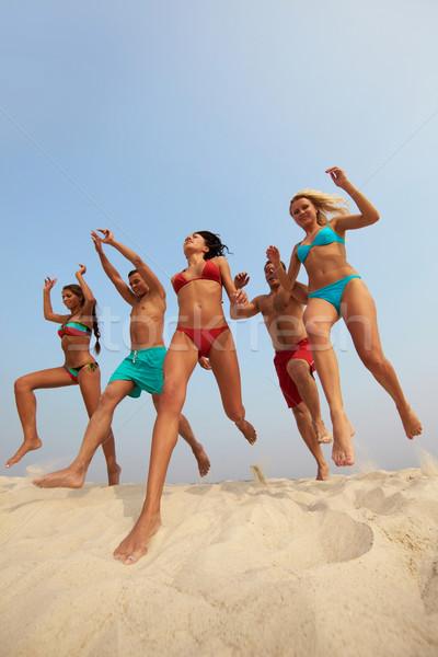 Dinamizmus portré boldog barátok ugrik homokos Stock fotó © pressmaster