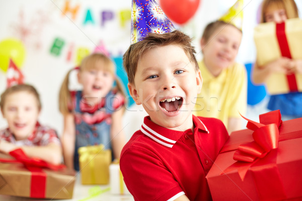 Joyful boy with giftbox looking at camera with his friends on background Stock photo © pressmaster