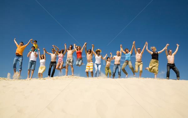 Dynamisch mensen menigte vrienden springen zandstrand Stockfoto © pressmaster