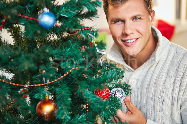 Man by decorated tree Stock photo © pressmaster