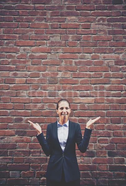 изображение нетерпеливый деловая женщина открытых ладонями кирпичная стена Сток-фото © pressmaster