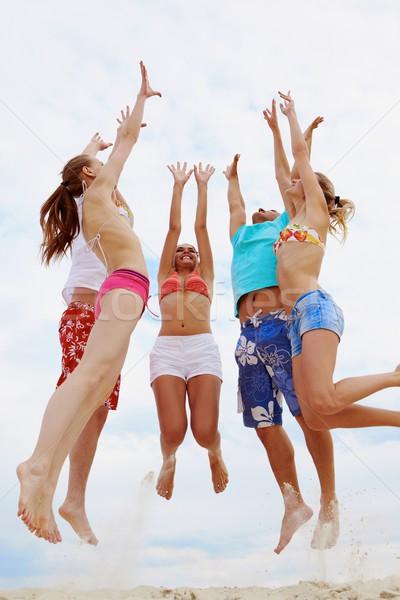 Hoogspringen foto vijf vrienden zandstrand hemel Stockfoto © pressmaster