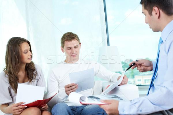 Seguro programa jovens olhando documentos encontrar Foto stock © pressmaster