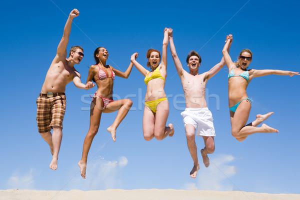 радостный команда друзей , держась за руки другой прыжки Сток-фото © pressmaster