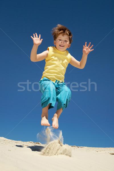 Kellemes vidám fiú ugrik homok néz kamera Stock fotó © pressmaster