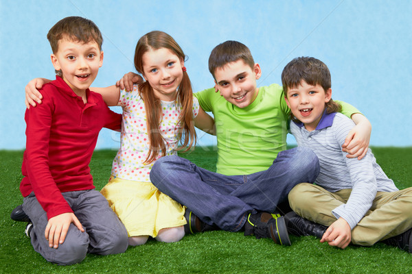 Gruppo bambini quattro seduta erba verde famiglia Foto d'archivio © pressmaster