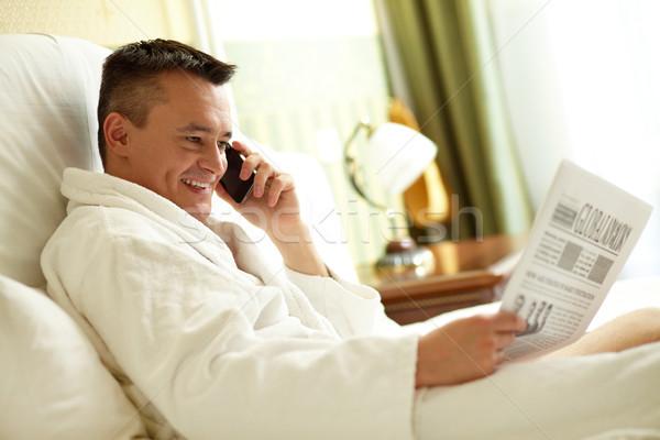 Okuma konuşma yakışıklı adam bornoz telefon gazete Stok fotoğraf © pressmaster