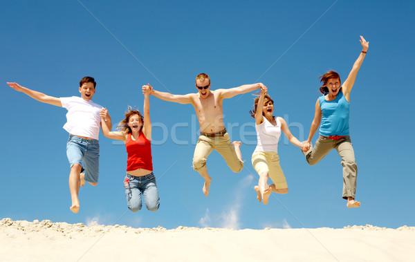 Dynamisme foto opgewonden mensen springen zandstrand Stockfoto © pressmaster