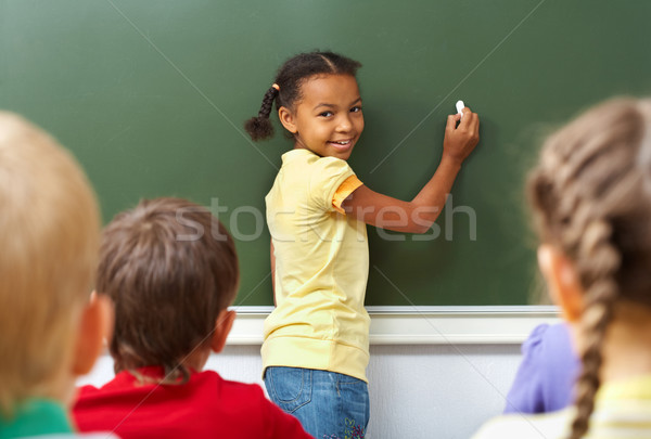 Iskolás lány kép iskolatábla néz kamera osztálytársak Stock fotó © pressmaster