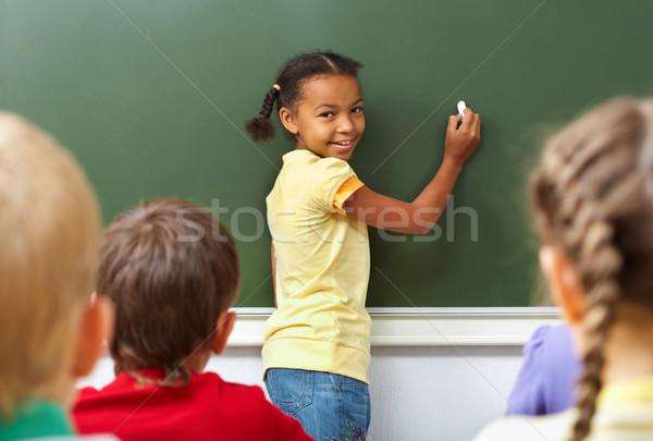 Schoolmeisje afbeelding Blackboard naar camera klasgenoten Stockfoto © pressmaster