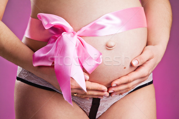 Pregnant belly with pink ribbon Stock photo © prg0383