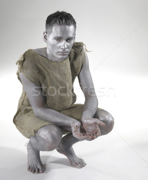 bodypainted poor man cowering on the ground Stock photo © prill
