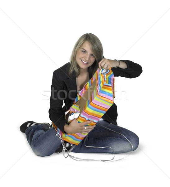sitting cute girl unwrapping a present Stock photo © prill
