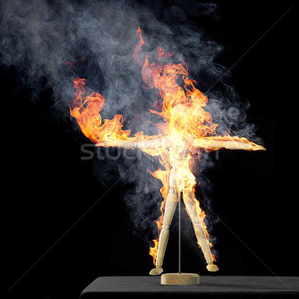 burning wooden doll on desktop Stock photo © prill