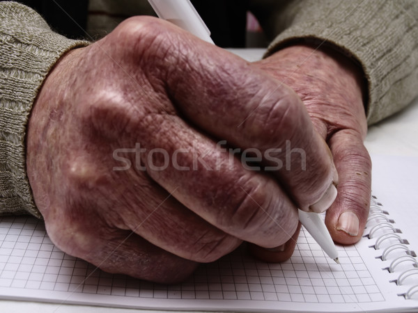 Closeup of the wrinkled hands of an old caucasian man holding pen and paper Stock photo © Pruser