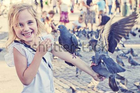 Smiling girl with pigeons on the hand Stock photo © przemekklos