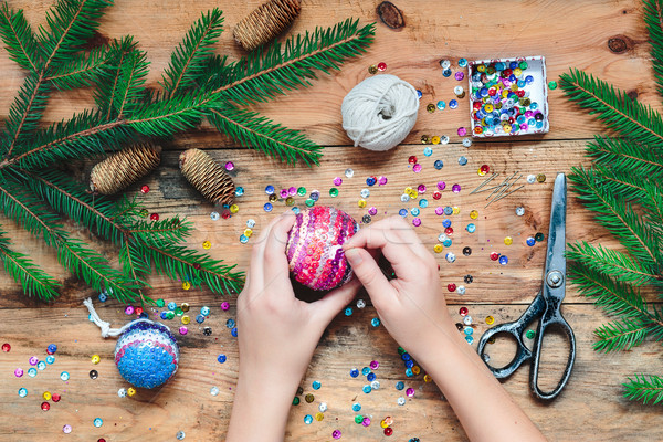Girl making Christmas ball pinning the sequins onto the ball Stock photo © przemekklos