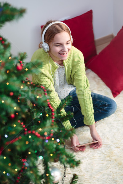 Girl listening to Christmas carols Stock photo © przemekklos