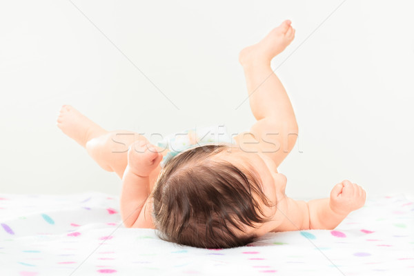 Back view of little baby girl lying on polka dots blanket Stock photo © przemekklos