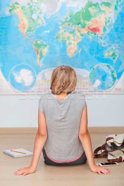 Girl sitting by the map in classroom Stock photo © przemekklos