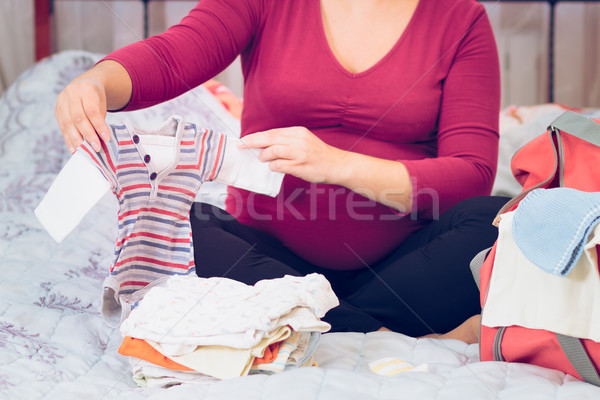 Pregnant woman packing hospital bag preparing for labor Stock photo © przemekklos