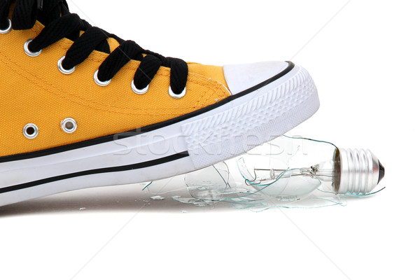 Stock photo: fragments of bulb under sneaker