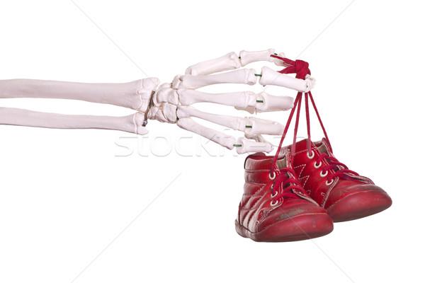 Csontváz kéz tart öreg piros babacipők Stock fotó © pterwort