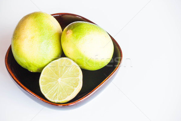 Fresh citrus limes whole and slice in bowl on white background Stock photo © punsayaporn