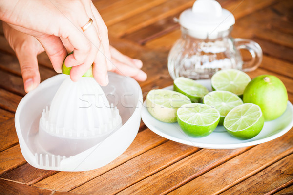 Hand squashing fresh citrus lime on wood table Stock photo © punsayaporn