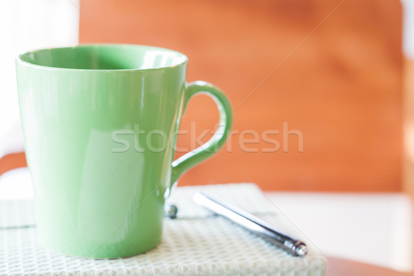 Closeup green mug with pen and notebook Stock photo © punsayaporn