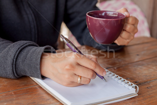 Woman hand with pen writing on notebook Stock photo © punsayaporn
