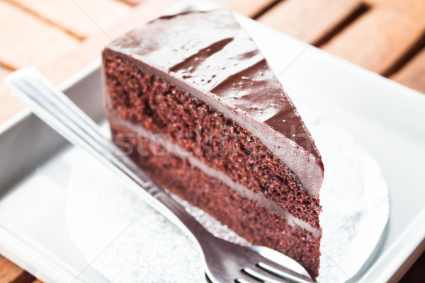 Chocolate cake serving on white plate with spoon and fork Stock photo © punsayaporn