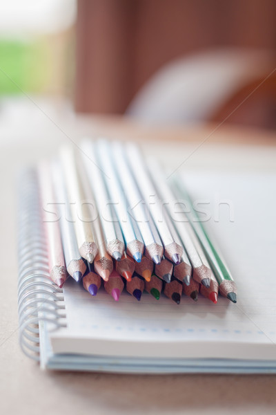 Cluster of colorful pencil crayons with spiral notebook Stock photo © punsayaporn
