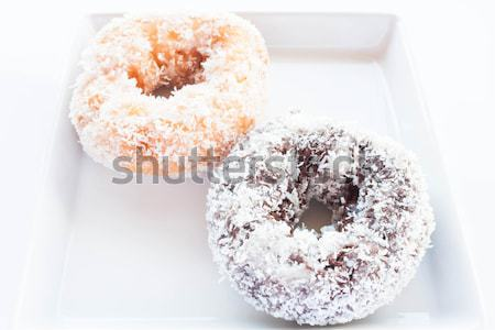 Chocolate and vanilla coconut donuts on white plate Stock photo © punsayaporn