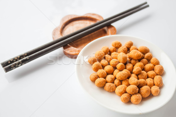 Spicy peanuts snack and chopsticks on white table  Stock photo © punsayaporn