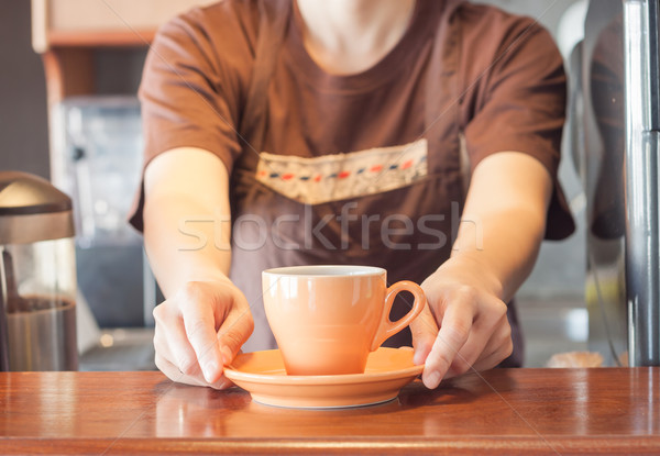Barista offering orange cup of coffee Stock photo © punsayaporn