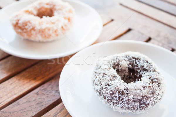Delicious chocolate and vanilla coconut donuts on wooden table Stock photo © punsayaporn