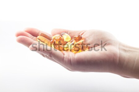 Hand holding fish oil capsules on white background Stock photo © punsayaporn