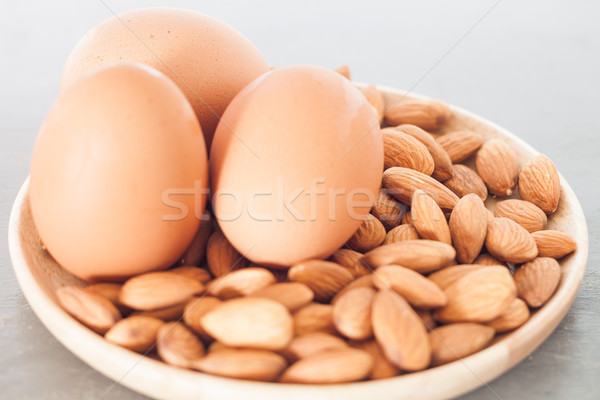 Almond nuts and eggs on wooden plate Stock photo © punsayaporn