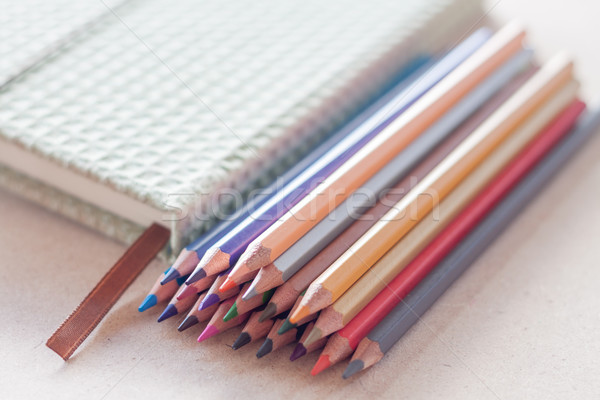 Stock photo: Cluster of colorful pencil crayons with green notebook