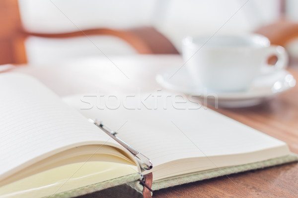 Stock photo: Open a blank white notebook and pen with a cup of coffee